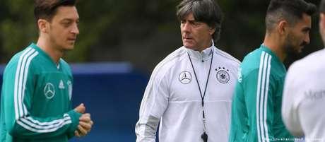 Joachim Löw, ao fundo, comanda treino com Özil (esq.) e Gündogan (dir.) já na Rússia