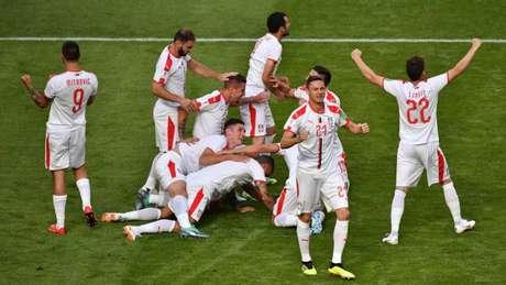 Jogadores da Sérvia vibram após o golaço de falta de Koralov (Foto: AFP/FABRICE COFFRINI)