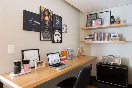 6. Escritório com muitos quadros e peças de madeira. Projeto de Doob Arquitetura