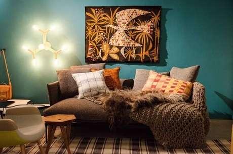 4. Sala de estar turquesa com sofá marrom com manta de tricô. Projeto de Casa Cor SP 2017