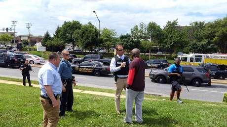 Policiais conversam com sobrevivente do ataque à redação do jornal.