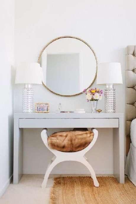 22. Modelo de penteadeira branca com espelho redondo com moldura dourada para dar um toque de requinte na decoração clean