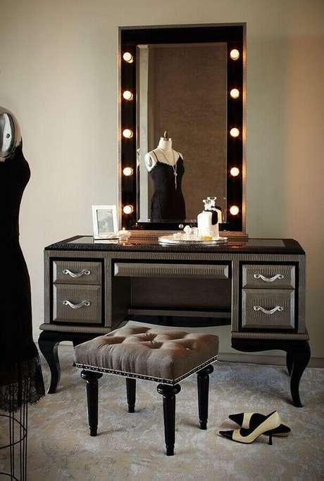 32. Decoração sofisticada com modelo preto de penteadeira com espelho camarim