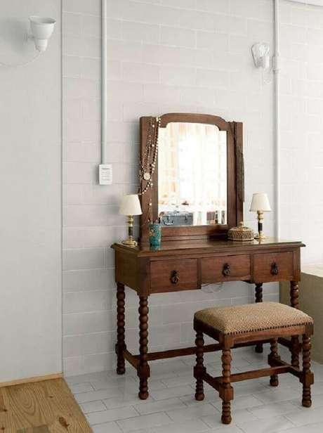 36. A penteadeira com espelho feita de madeira é garantia de um toque rústico e confortável à decoração
