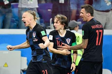Modric, entre o zagueiro Vida e o atacante Manduzic, vibra muito. Afinal, após jogo dramático com a Dinamarca, só decidido nos pênaltis, a Croácia avança para as quartas de final da Copa e vai encarar a Rússia (AFP)