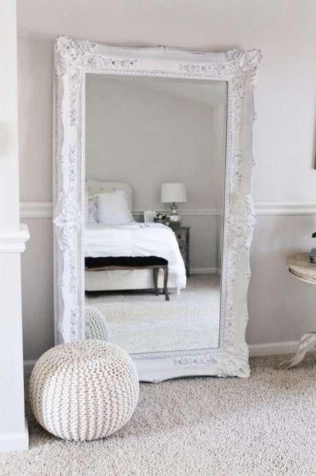 1. Espelho grande para quarto com moldura branca e clássica deixando a decoração mais sofisticada e delicada.