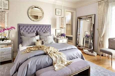 3. Decoração para quarto de casal em tons de lilás e com espelho grande para quarto se tornando o grande destaque no ambiente.