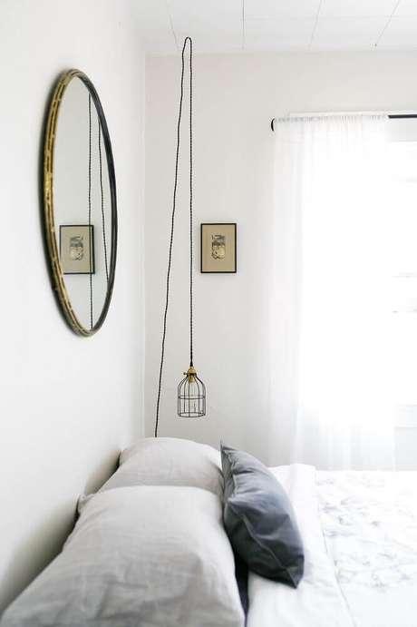 38. A decoração minimalista fica mais charmosa com o espelho para quarto com moldura em ouro envelhecido