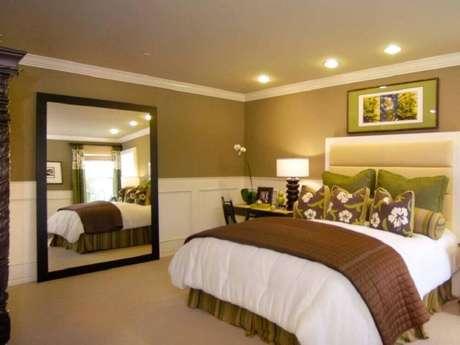 46. Moldura de madeira para espelho grande para quarto de casal com decoração em tons neutro