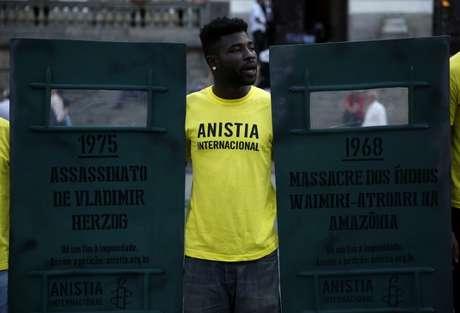 """Manifestante com camiseta da Anistia Internacional protesta no aniversário de 50 anos do golpe de 1964, ao lado de um escudo com os dizeres """"1975 - Assassinato de Vladimir Herzog"""" 01/04/2014 REUTERS/Pilar Olivares"""