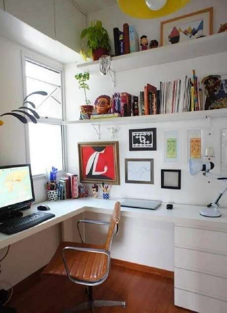 6. Home office tudo branco com mesa de canto para computador e prateleiras para organizar livros e objetos de decoração