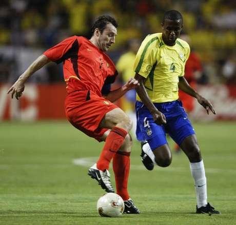 O então atacante Marc Wilmots tenta passar pelo brasileiro Roque Júnior, na Copa de 2002
