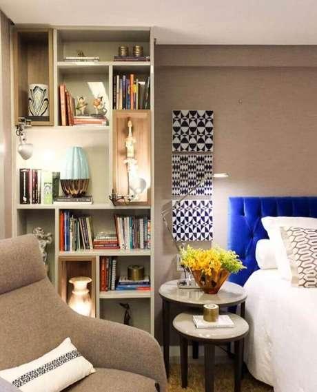 38. Estante feita com nichos para quarto com cabeceira estofada azul