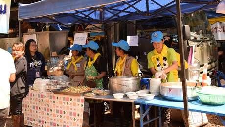 Voluntários e funcionários da cozinha real tailandesa preparam refeições para todos no acampamento da operação de resgate