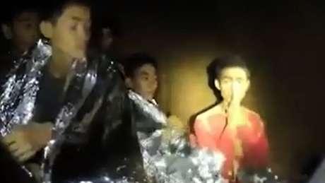 Adul Samon (à direita, com as mãos unidas) chamou a atenção por cumprimentar os mergulhadores com um gesto tradicional de respeito, na tradição tailandesa. Ele se comunicou em inglês com os dois britânicos que acharam o grupo, após uma semana de buscas na caverna. Samon é refugiado de uma região de conflito de Mianmar e vive longe dos pais