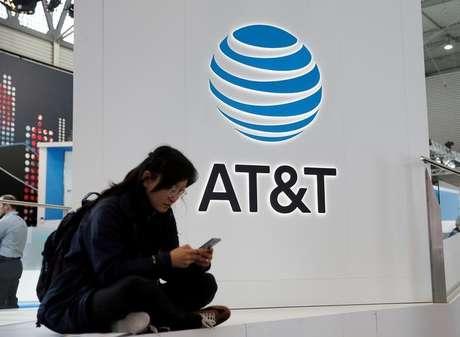 Mulher usa celular diante de logo da AT&T durante congresso em Barcelona, Espanha 25/02/2016 REUTERS/Albert Gea/File Photo