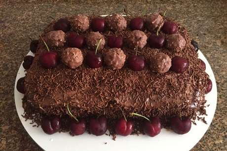 Bolo mousse de chocolate decorado com cerejas e bombons