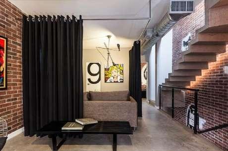 14. Casa decorada com parede de tijolinho e cortina divisória de ambiente preta