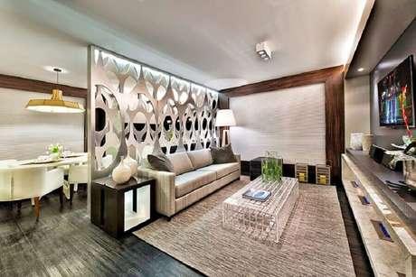 4. Decoração moderna e sofiticada para salas integradas separadas por divisórias para sala com placas vazadas em formato circular