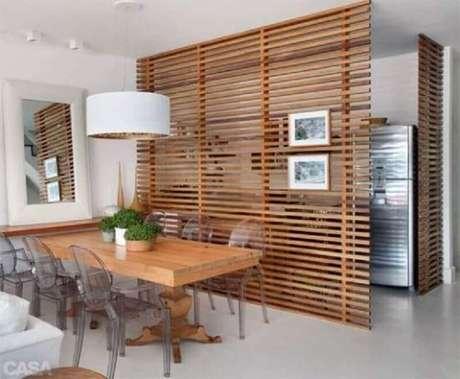 41. Painel com vigas de madeira como divisória para sala de jantar com cadeiras de acrílico transparente