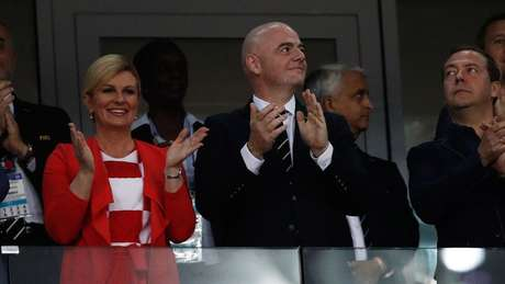 A croata assistiu à partida em que sua seleção eliminou a Rússia ao lado do presidente da Fifa, Gianni Infantino (ao centro), e do primeiro-ministro russo, Dmitry Medvedev (à direita).