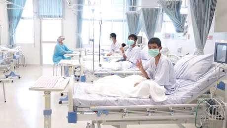 Captura de tela mostra meninos resgatados de caverna na Tailândia usando máscaras em hospital em Chiang Rai
