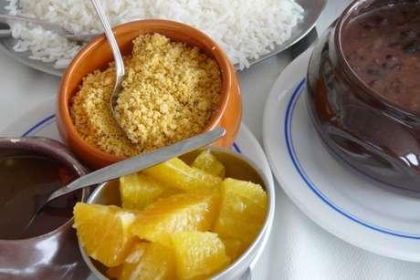 Feijoada acompanhada de um recipiente com laranjas fatiadas e outro com farofa