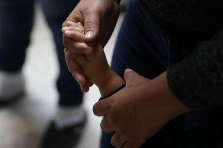 Mulher segura mão de criança à medida que famílias imigrantes são liberadas em McAllen, Texas 22/06/2018 REUTERS/Loren Elliott