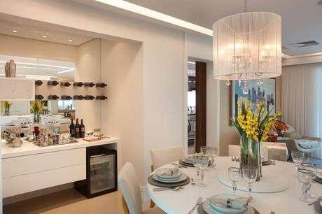 4 – Crie um anexo interessante no ambiente com o auxílio do buffet para sala de jantar, como o bar organizado sobre esse buffet branco