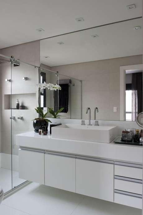 42. Os banheiros planejados podem contar com espelho até o teto para ampliar visualmente o espaço. Projeto por Jamile Lima