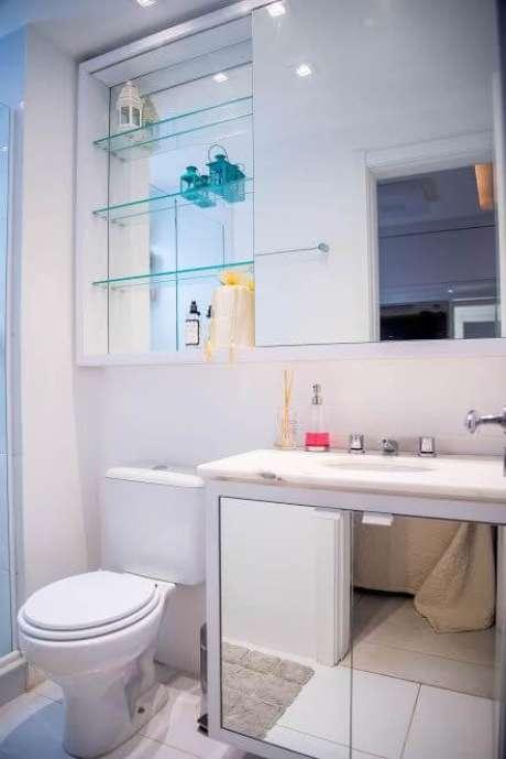 26. O armário e a espelheira espelhados com as prateleiras de vidro deixam o ambiente visualmente maior. Projeto de Roberta Menna Barreto