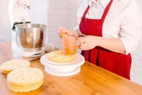 Mulher regando massa do bolo com calda