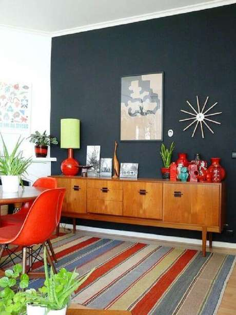 25 – Buffet de madeira para sala de jantar com tapete colorido e itens de decoração em vermelho e turquesa