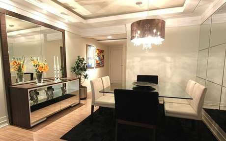 26 – Aqui, o buffet para sala de jantar com espelho grande ajudou a deixar a decoração bem sofisticada e iluminada
