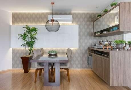 31 – Decoração de sala de jantar com papel de parede de losango e buffet de madeira combinando com o armário aéreo