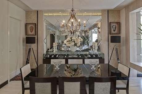37 – Decoração sofisticada com lustre e buffet para sala de jantar com superfície feita de vidro