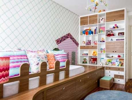 41. Quarto de bebê menina com almofadas coloridas e estante com nichos. Projeto de Anna Maria Parisi