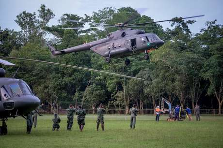 Helicóptero da Força Aérea tailandesa leva uma mini-escavadeira à montanha