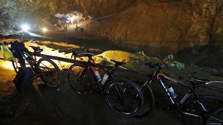 Bicicletas e mochilas deixadas pelos meninos do lado de fora da caverna