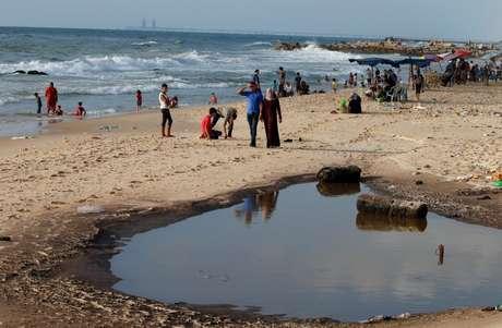 Palestinos em praia poluída de Gaza 13/07/2018 REUTERS/Mohammed Salem