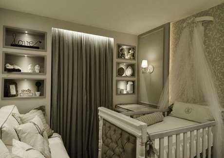 32. O quarto de bebê pequeno planejado com decoração sofisticada graças à cabeceira capitonê do berço e os nichos embutidos com iluminação