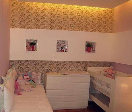 37. Alguns modelos de papel de parede não possuem listras, mas graças a suas estampas na vertical, eles também são perfeitos para o quarto de bebê simples e pequeno