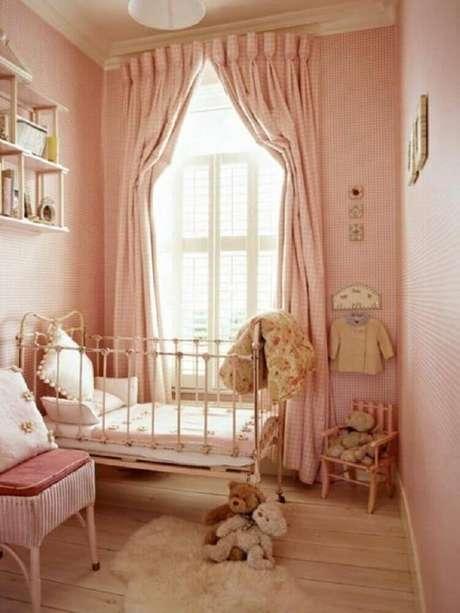 41. Decoração em tons de rosa e com piso de madeira para quarto pequeno de bebê