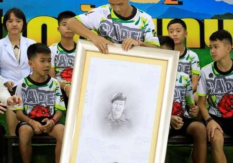 Os 13 resgatados seguraram uma ilustração a lápis de Samarn Kunan, o mergulhador que morreu durante as operações de resgate