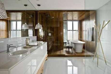 2. Piso para banheiro de porcelanato em uma parte e madeira em outra. Projeto por Leo Romano