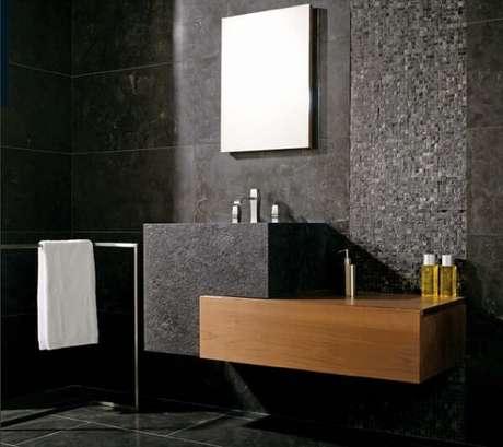 7. Banheiro revestido com parede de pedras naturais combina com o piso cerâmico.