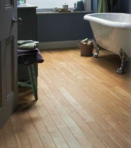 46. O piso para banheiro em madeira deixa o ambiente super charmoso e aconchegante