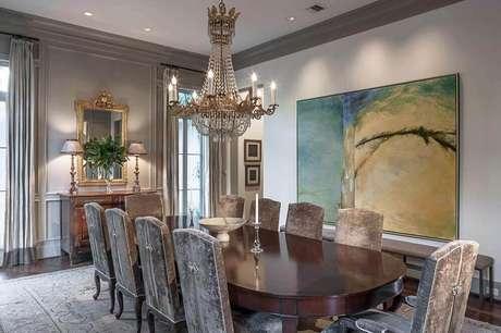9. Decoração clássica para sala de jantar com lustre sofisticado e quadro grande