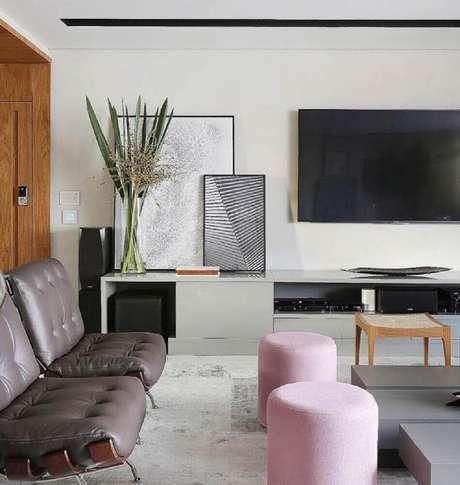 2. Decoração com quadros grandes para sala de estar apoiados sobre a rack