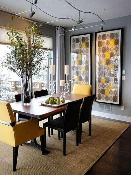 5. Sala de jantar com estilo moderno decorada com quadros grandes e spots de luz